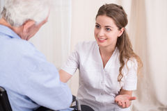 Krankenschwester, die mit älterem Mann spricht lizenzfreie stockbilder