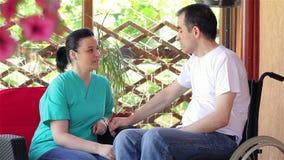 Krankenschwester, die mit jungem Mann im Rollstuhl spricht stock video footage