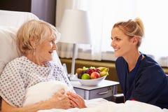 Krankenschwester, die mit älterem weiblichem Patienten im Krankenhaus-Bett spricht Lizenzfreie Stockfotos