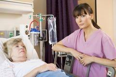 Krankenschwester, die oben auf dem Patienten liegt im Krankenhaus-Bett überprüft Lizenzfreie Stockfotografie