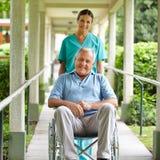 Krankenschwester, die Rollstuhl drückt Stockfotografie