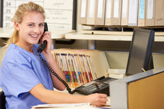 Krankenschwester, die Telefon-Aufruf an der Krankenschwester-Station macht Stockbilder