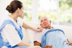 Krankenschwester, die um krankem älterem Patienten sich kümmert Stockbild