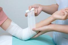 Krankenschwester, die Verband am geduldigen Ellbogen anwendet stockfoto