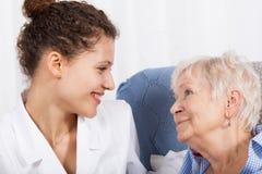 Krankenschwester, die Zeit mit älterer Dame verbringt Stockbilder