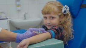 Krankenschwester entnimmt Blutprobe von einer Ader im Arm des kleinen Mädchens Lizenzfreies Stockfoto