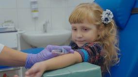 Krankenschwester entnimmt Blutprobe von einer Ader im Arm des kleinen Mädchens Lizenzfreie Stockfotos