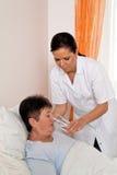 Krankenschwester in gealterter Sorgfalt für die älteren Personen Stockfotografie