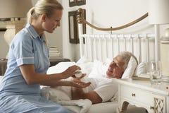 Krankenschwester-Giving Senior Male-Medikation im Bett zu Hause Stockfotos