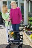 Krankenschwester Helping Senior Woman, zum mit Wanderer zu gehen stockfoto