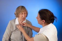 Krankenschwester hilft einer älteren Frau mit dem Kleiden Stockfotografie