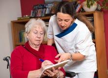 Krankenschwester hilft einer alten Frau Stockbild