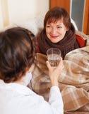 Krankenschwester im einheitlichen Interessieren für ältere Frau Stockbilder
