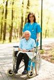Krankenschwester mit älterer Dame im Rollstuhl Lizenzfreies Stockbild