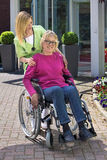 Krankenschwester mit älterer Frau im Rollstuhl draußen Stockfotografie