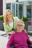Krankenschwester mit älterer Frau im Rollstuhl draußen Lizenzfreie Stockfotografie