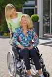 Krankenschwester mit älterer Frau im Rollstuhl draußen Lizenzfreie Stockfotos