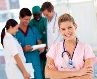 Krankenschwester mit Doktoren im Hintergrund Stockfoto