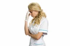 Krankenschwester mit starken Kopfschmerzen auf Weiß Stockbilder