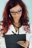 Krankenschwester mit Stethoskopschreibensdiagnose Stockbilder