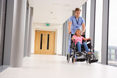 Krankenschwester-Pushing Girl In-Rollstuhl entlang Korridor Stockfotografie
