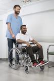 Krankenschwester-Pushing Patient In-Rollstuhl am Krankenhaus-Korridor Stockfotos