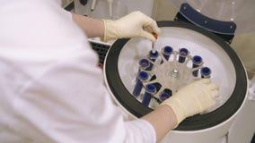 Krankenschwester Putting Blood Samples in der zentrifugalen Maschine stock video