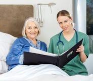 Krankenschwester And Senior Woman mit ärztlichen Attesten herein Lizenzfreies Stockbild