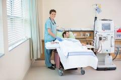 Krankenschwester Standing By Patient, das herein Dialyse empfängt Lizenzfreie Stockfotos