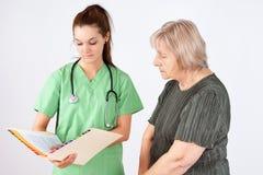 Krankenschwester und ältere Lesekrankengeschichte Stockbild