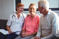 Krankenschwester und ältere Paare, die auf einer Couch sitzen Lizenzfreie Stockfotos