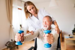 Krankenschwester und älterer Mann im Rollstuhl während des Hausbesuchs Lizenzfreie Stockfotos