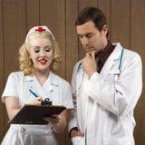 Krankenschwester und Doktor, die Klemmbrett betrachten. stockfotografie