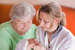 Krankenschwester wäscht Hände einer älteren Frau Stockfotos