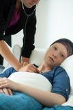 Krankenschwester, welche die Atmung des Patienten überprüft Lizenzfreie Stockbilder