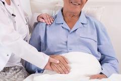 Krankenschwester, welche die Hand des Patienten hält stockfoto