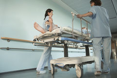 Krankenschwestern, die Patienten auf Rollbahre im Krankenhaus-Korridor befördern Stockbilder