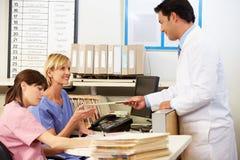 Krankenschwestern Doktor-With zwei, die an der Krankenschwester-Station arbeiten Stockfotografie