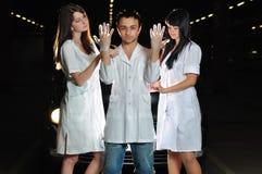 Krankenschwestern helfen dem Chirurgen, Handschuhe zu kleiden lizenzfreie stockfotos