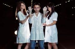 Krankenschwestern helfen dem Chirurgen, Handschuhe zu kleiden stockfoto