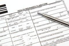 Krankenversicherung-Antragsformular mit silberner Feder stockbild