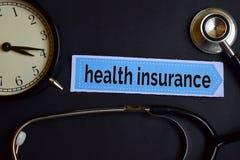 Krankenversicherung auf dem Druckpapier mit Gesundheitswesen-Konzept-Inspiration Wecker, schwarzes Stethoskop lizenzfreie stockfotografie