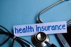 Krankenversicherungsaufschrift mit der Ansicht des Stethoskops, der Brillen und des Smartphone auf dem blauen Hintergrund lizenzfreie stockbilder