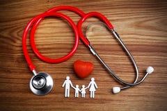 Krankenversicherungskonzept Familien-Ausschnitt und Stethoskop auf hölzernem Hintergrund stockbild