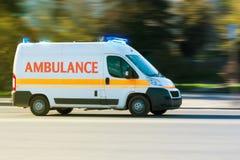 Krankenwagen auf Notruf in der Bewegungsunschärfe mit blauem Blinklicht Stockbilder