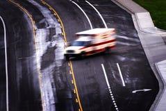 Krankenwagen, der hinunter die Fahrbahn verwischt beschleunigt Lizenzfreie Stockfotografie