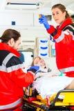Krankenwagen, welche verletzter Frau mit Infusion hilft Stockfotografie