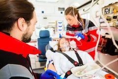 Krankenwagen, welche verletzter Frau mit Infusion hilft Lizenzfreie Stockfotos