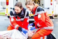 Krankenwagendoktor, der dem weiblichen Opfer Sauerstoff gibt stockbild
