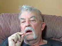 Kranker älterer Mann, der Medizinpillen einnimmt. Lizenzfreies Stockfoto